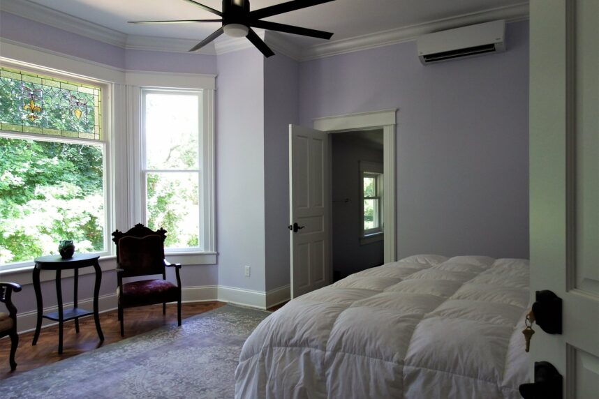 Lavender room with large bay window, 2 chairs and a table, stained glass window and ceiling fan