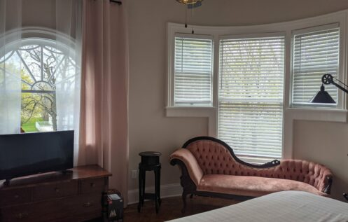 bedroom with fainting couch in front of a curved bank of windows