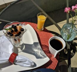 outdoor table setting with fruit parfait, orange juice and a cup of coffee